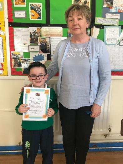 Theo pictured with his certificate for completing the Reading Partnership Programme.