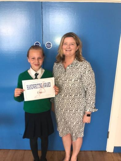 Ema pictured with her Handwriting Award presented by Mrs Smith